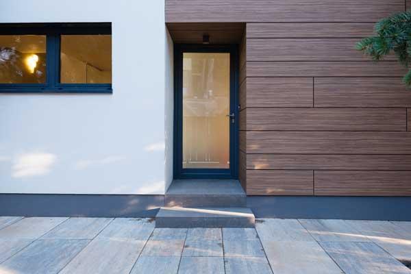 Façade d'une maison moderne en béton et en bois. Porte d'entrée en verre.