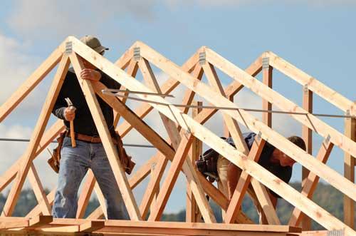 Charpentier effectuant des travaux sur une charpente en bois d'une maison