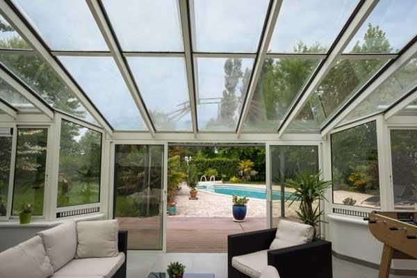 veranda aménagée donnant sur une terrasse et piscine