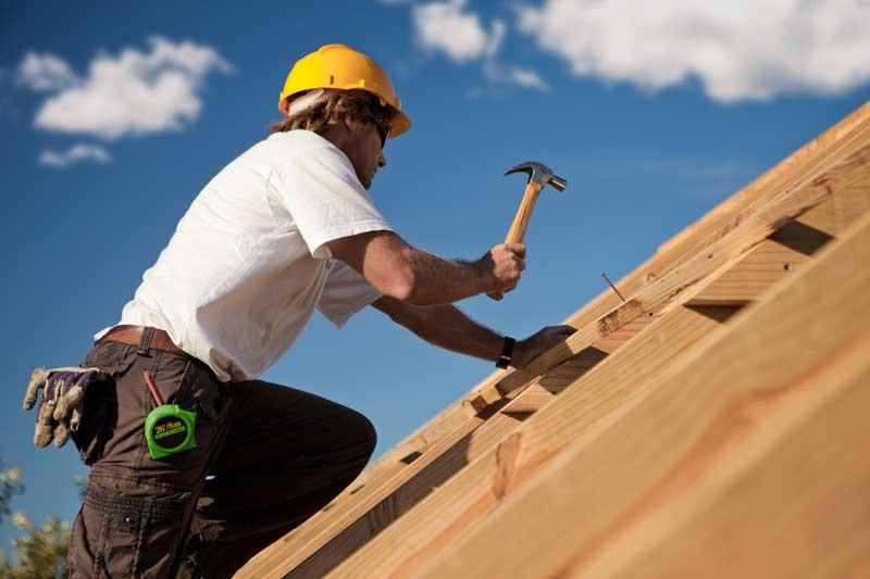 couvreur charpentier entreprise couverture entrain de travailler sur la charpente d'un toit